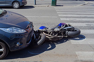 Motorcycle under car after crash